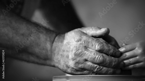 Hands of old potter and young follower