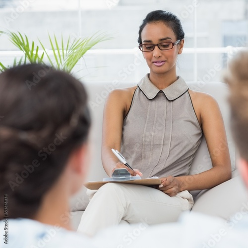 Therapist talking with couple on the couch and taking notes