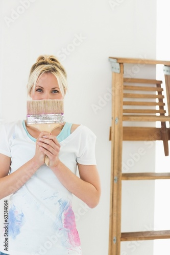 Woman holding paint brush in front of her face at new house