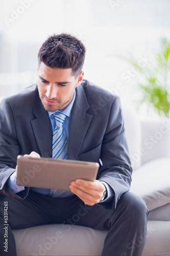 Businessman sitting on sofa using his tablet pc