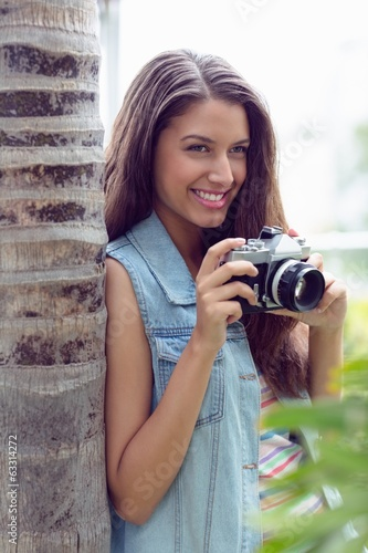 Stylish young girl taking photographs outside