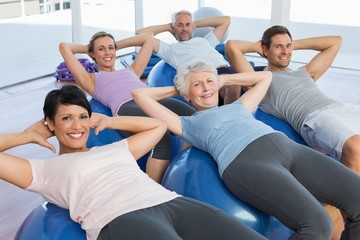 Smiling people stretching on exercise balls
