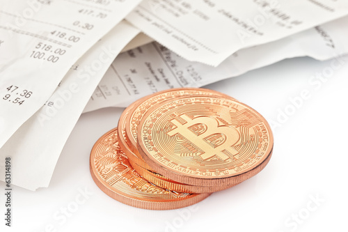 Photo .Golden Bitcoins (new virtual money ) and paper receipts