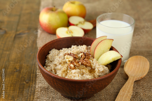 Tasty oatmeal with nuts and apples on wooden table