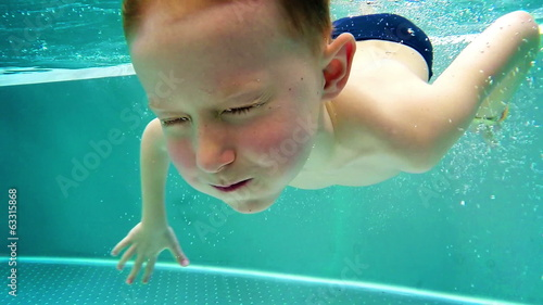 Slowmotion: Playfull boy dives in hot winter pool