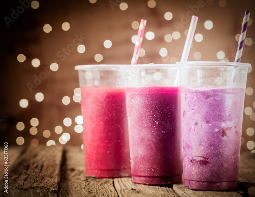 Three colorful berry smoothies with party lights