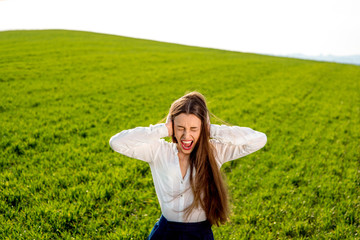 Lonely girl crying in the green field with cloudy sky