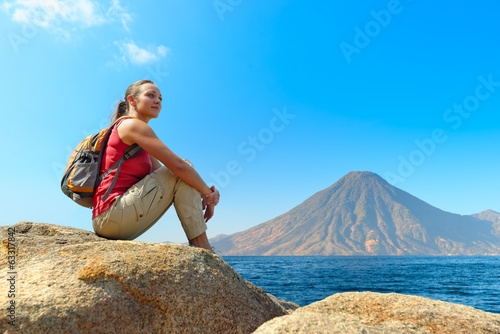 Hiker with backpack relaxing on a rock