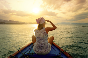 Woman traveling by boat at sunset among the islands