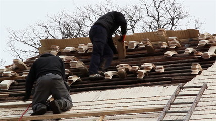Two roofers arranging the wooden shingles