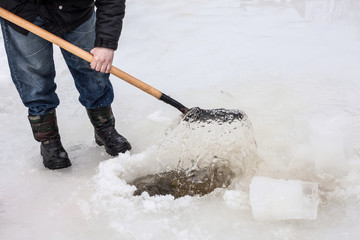 man scoops chunks of ice out of the hole