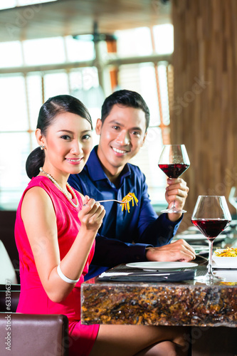 Portrait of Asian couple eating in restaurant