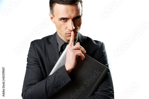 Businessman holding laptop and showing silence sign