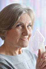 Elderly woman doing inhalation