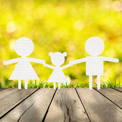 Family standing with spring green grass with bokeh and sunlight