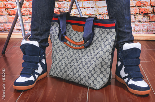 fashionable women bag and feet in jeans