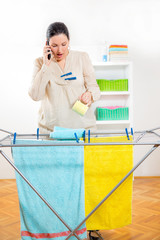 Woman hanging clothes and using a phone