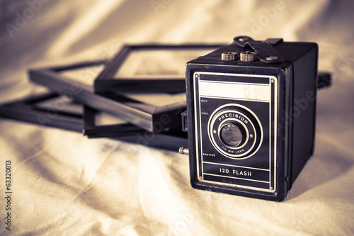 Vintage box camera and framed pictures with retro toning