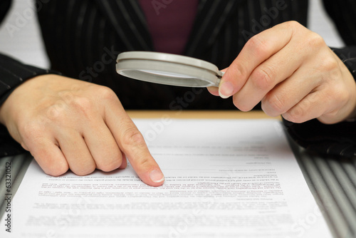 Businesswoman looking through a magnifying glass to contract