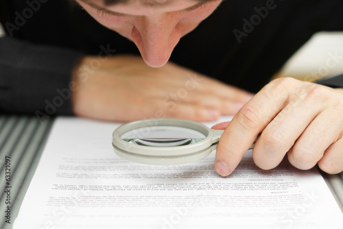 Businessman looking through a magnifying glass to document