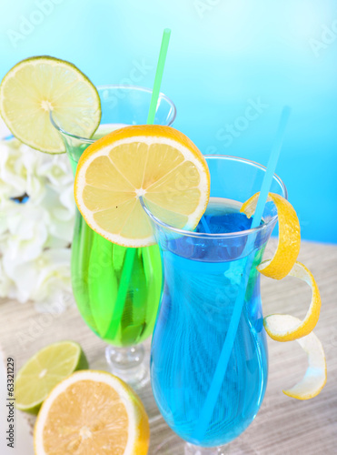 Glasses of cocktails on table on light blue background