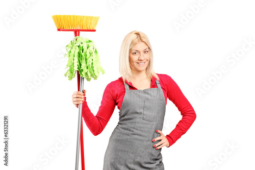Female cleaner holding a mop and a broom