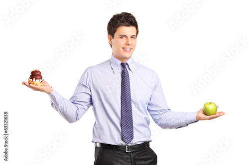 Man holding an apple and a cake