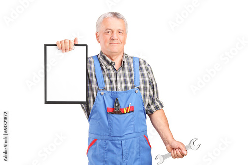 Mature mechanic holding wrench and a clipboard