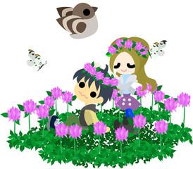 アカツメクサの花畑で花冠を作るカップル。