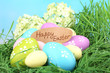 Easter composition with eggs on green grass, on blue background