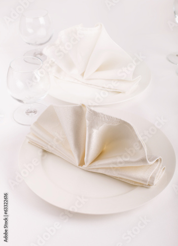 Table appointments with plates, napkins and wine glasses