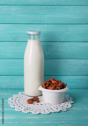 Almond milk in bottle with almonds in bowl,