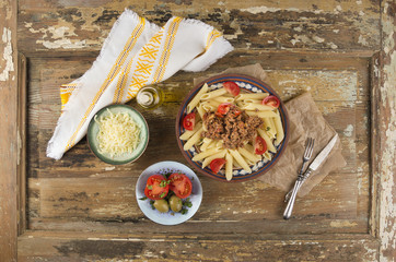 penne pasta with bolognese sauce, bowls of snacks