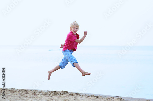 Happy active boy jumping on the beach