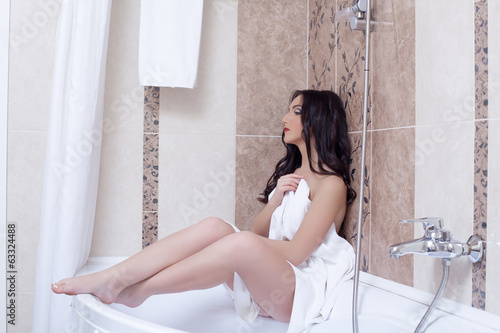 Image of attractive girl posing in hotel bathroom