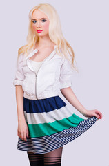 Beautiful blonde girl in skirt with stripes