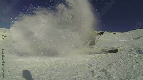 Skier spraying snow at camera in slow motion
