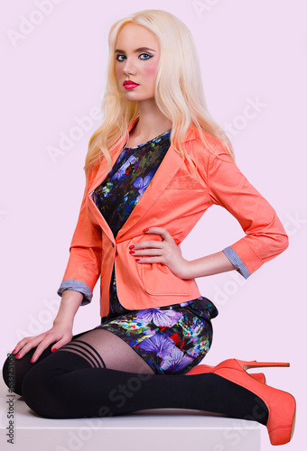 Beautiful fashionable blonde girl in orange jacket