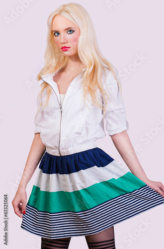 Beautiful fashionable blonde girl in skirt with stripes