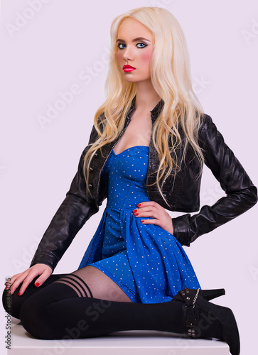 Beautiful fashionable blonde girl sitting on chair