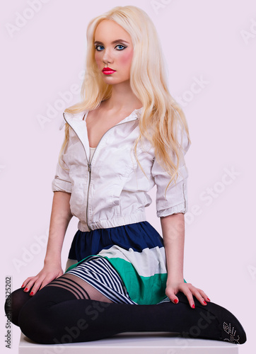 Beautiful blonde girl sitting on chair
