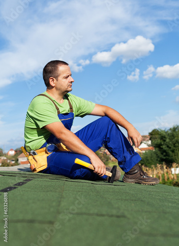 Roofer worker resting on top of building