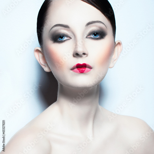 Portrait of a beautiful woman like doll with a glamorous cool ma