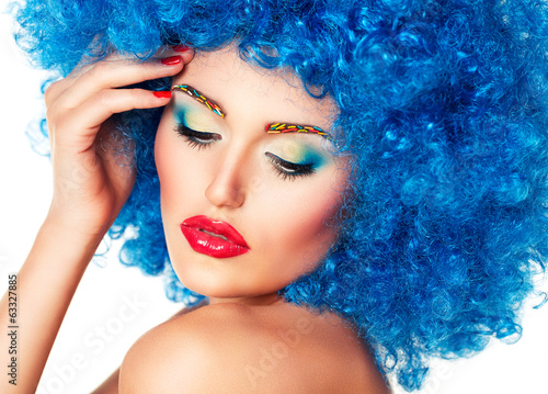 Portrait of a young beautiful girl with bright makeup in blue wi