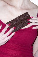 Woman holds a tile of milk chocolate in hand