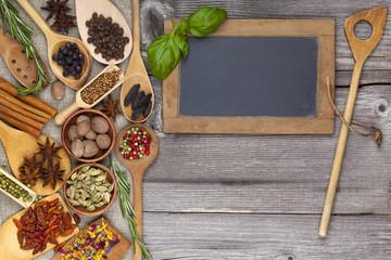 Kräuter und Gewürze mit Kochlöffel und Tafel