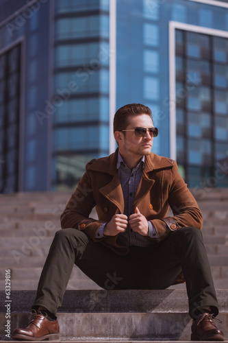 handsome man is sitting on a skyscraper background
