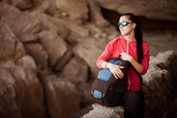 Young lady hiker with backpack in the cave