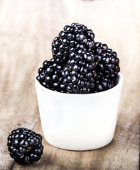 Fresh Blackberries in a white bowl on  wooden table close up wit