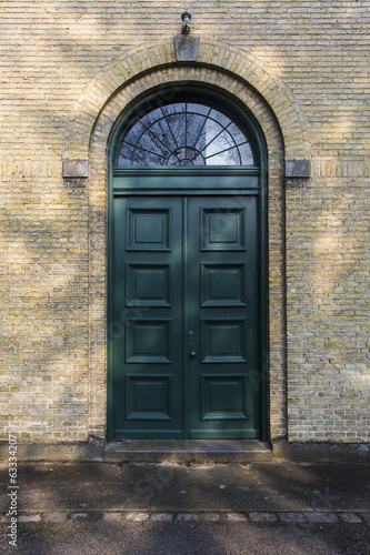 Old green door in yellow brick wall